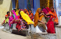Hindu women dressed in colorful sari in indian street market orange red green yellow and blue trading and choosing different goods Royalty Free Stock Photo