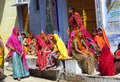 Hindu women dressed in colorful sari in indian street market orange red green yellow and blue trading and choosing different goods Royalty Free Stock Images