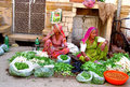 Hindu women in indian street market dressed colorful orange red green yellow and blue sari trading and selling different food Royalty Free Stock Photos