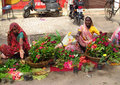 Hindu women in indian street market dressed colorful orange red green yellow and blue sari trading and selling different food Stock Photo