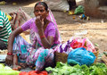 Hindu women in indian street market dressed colorful orange red green yellow and blue sari trading and selling different food Royalty Free Stock Photography