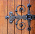 Hinge forged iron door and rivets on an old wooden door Royalty Free Stock Photo
