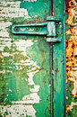 Hinge on rusty metal door with cracked paint Royalty Free Stock Photo