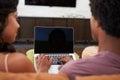 Hintere ansicht von den paaren die auf sofa using laptop sitzen Lizenzfreies Stockbild