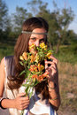 Hippie girl smells lily outdoors Royalty Free Stock Image