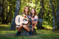 Hippie girls with guitar in a forest sitting on the stump Royalty Free Stock Photo