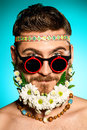 Hippie life handsome smiling young man in glasses and a beard of flowers Stock Image
