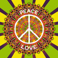 Hippie peace symbol. Peace and love sign on ornate colorful mandala background. Royalty Free Stock Photo