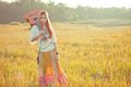 Hippie woman walking in golden field with acoustic guitar Royalty Free Stock Photography