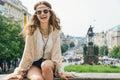 Hippy-looking woman tourist sitting on stone parapet in Prague Royalty Free Stock Photo
