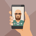 Hipster bearded young man takes selfie using a smartphone.