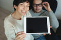 Hipster couple in eyewear showing the screen of tablet young sitting on chair apartment Stock Images