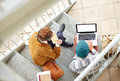 Hipster couple using computer and eating lunch outdoors sitting in stairs at university campus Stock Images