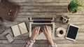 Hipster desktop with male hands vintage wooden top view typing on a laptop Stock Image