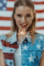 Hipster girl in american patriotic outfit holding sparkler with us flag on background Royalty Free Stock Photo
