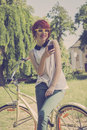 Hipster girl on her vintage bike listening to the music retro teenage purple smart phone colors toned image Royalty Free Stock Photo