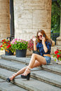 Hipster girl in shirt and denim shorts on phone seductive a sunglasses sitting the steps woman talking cell the concept of Royalty Free Stock Photo