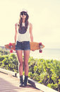 Hipster girl with skate board wearing sunglasses beautiful Royalty Free Stock Images