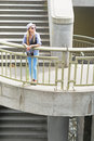 Hipster girl standing on stairs in city hat Stock Images