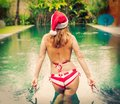 Hipster girl wearing Santa hat in the pool Royalty Free Stock Photo