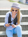 Hipster girl writing sms while sitting on stairs in hat Stock Image
