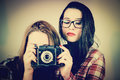 Hipster girls using an old camera serious taking pictures with film retro filter effect added Royalty Free Stock Image