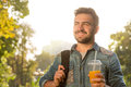 Hipster man walking in the park and drinking orange cocktail bearded short haired jeans shirt looking away Stock Photography