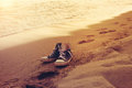 Hipster sneakers in a sea surf on a sand with footprints Royalty Free Stock Photo