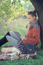 Hipster style young woman using tablet pc and eating an apple during a rest in the autumn park Stock Photos