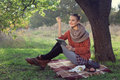 Hipster style young woman using tablet pc during a rest under the tree Royalty Free Stock Image