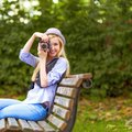 Hipster taking photo with retro photo camera sitting on be