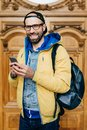 Hipster tourist in glasses, cap and yellow anorak holding backpack and smartphone having excursion in art gallery making photos be Royalty Free Stock Photo