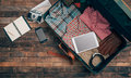 Hipster traveler packing vintage open suitcase on a wooden table with clothing camera and mobile phone top view Stock Photos