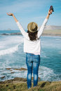 Hipster woman enjoy freedom on vacation travel successful funky girl raising arms towards the sea in asturias spain Stock Image