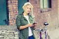 Hipster woman portrait with phone and bike Royalty Free Stock Photo