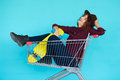 Hipster woman with yellow skateboard sitting in shopping trolley Royalty Free Stock Photo