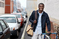Hipster work commute young trendy black african man with bicycle walking in urban city on way to Royalty Free Stock Image