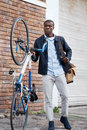 Hipster work commute young trendy black african man with bicycle walking in urban city on way to Stock Photography
