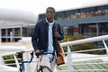 Hipster work commute young trendy black african man with bicycle walking in urban city on way to Royalty Free Stock Images