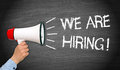 We are hiring chalkboard or blackboard with female hand and megaphone or loudspeaker Royalty Free Stock Photography