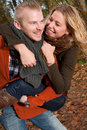 His girlfriend is smiling while riding piggyback happy young couple having a nice time in october Royalty Free Stock Photos