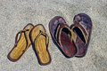 His and hers flip flop sandals on the sandy beach Royalty Free Stock Photo