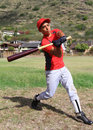 Hispanic baseball player mid-swing Royalty Free Stock Photos