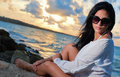 Hispanic beauty sitting by the ocean at sunset Royalty Free Stock Photo