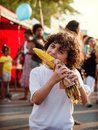 Hispanic boy eating corn in a street festival Royalty Free Stock Photography