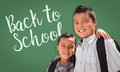 Hispanic Boys Wearing Backpacks In Front Of Back To School Written On Chalk Board