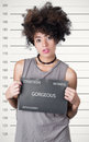 Hispanic brunette rebel model afro like hair wearing grey sleeveless shirt holding up police department board with number as Royalty Free Stock Image