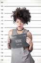 Hispanic brunette rebel model afro like hair wearing grey sleeveless shirt holding up police department board with number as Royalty Free Stock Images
