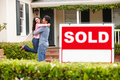 Hispanic couple outside home with sold sign Royalty Free Stock Photography