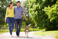 Hispanic couple taking dog for walk in countryside with arms around each other Stock Images